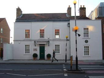 Symmetrical two storey 18th-century house, three windows wide, with additional bay to right. Built of brick, painted white. The central doorway has a doorhood. On the right-hand bay, a green plaque commemorates Cesar Picton. Zebra crossing to right.