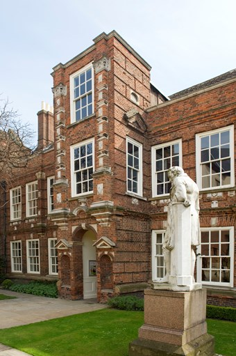 Large 17th-century house in Artisan Mannerist style. Two storeys, with a three-storey tower porch. Red brick with stone dressings. To right, a stone statue of William Wilberforce, seen from the side, standing and leaning on a column.
