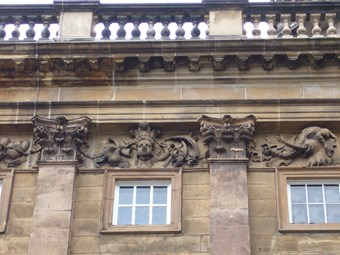Carved frieze at the top of an 18th-century building, with Corinthian pilasters below a balustraded parapet. At centre, an African woman wearing a feather headdress, surrounded by swags of fruit, tusks, and a parasol. An elephant head to right.