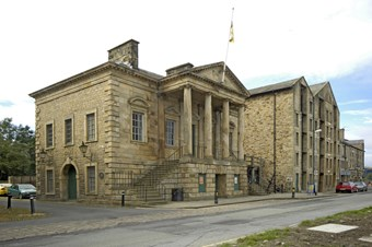 An 18th-century ashlar building in Classical style. It has a portico with four columns above a rusticated basement, with steps to either side. A flag flies from the pediment. Beside it to right is a tall rubblestone warehouse, of similar date.