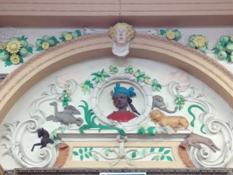 Tympanum with Rococo plasterwork, colourfully painted. Central roundel with head of a young African person in headdress. To left, an ostrich and a horse. To right, an elephant, lion and crocodile. Around, scrolled motifs with fruit, leaves and shells.