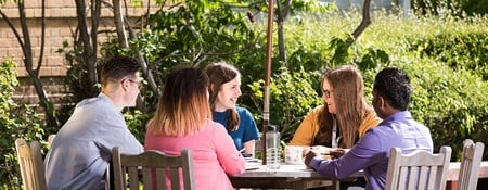 A group of younger Historic England employees in discussion seated at a table in a sunny courtyard.