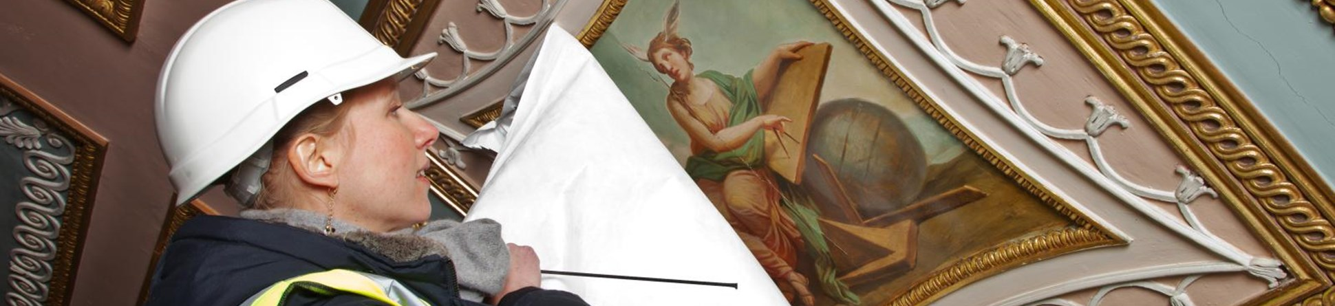 A woman peeling a protective sheet of a ceiling fresco.