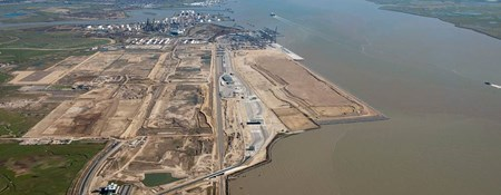 An oblique aerial colour photo of a London Gateway development, to the right is a large silty river, to the left a large industrial area.