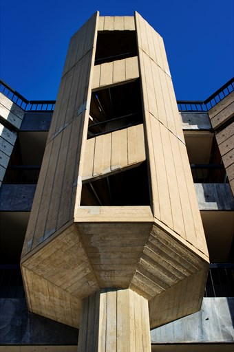 An octagonal stair turret in a gap on the front of a Brutalist university building.