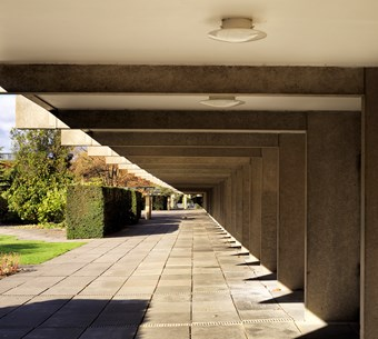 Low sun shining on a paved walkway. The raised ground floor allowing the ground underneath to be used - one of Le Corbusier's main features of Modernism.