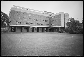 Black and white photo of three-storey building with ground floor raised on stilts leaving the ground space open. It has window ribbons and no ornamentation.