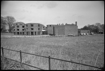 Black and white photo of three-storey hexagonal block building viewed across a field.