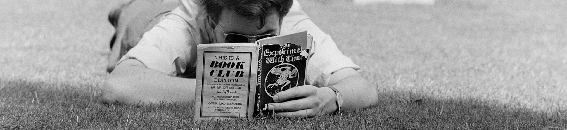 Black and white image of a man viewed head-on lying flat on the grass, engrossed in a book.
