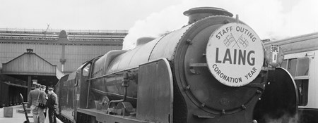 Steam train in station with a placard on the front which reads, 'LAING -  STAFF OUTING - CORONATION YEAR'