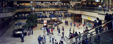 Colour photograph showing shoppers inside Queensgate shopping centre. The two levels of British Home Stores are in the background. On the right, shoppers are riding down an escalator into a large central square.