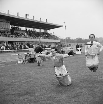 Two men jumping towards the finishing line of the men's sack race
