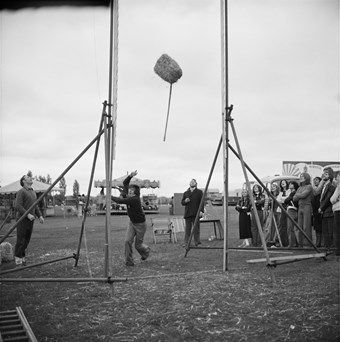 A man attempting to toss a hay bale over a pole with spectators watching on