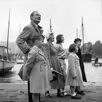 A side view of a man, women and children posed on a beach, with boats in the water beyond
