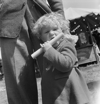 A toddler with curly blond hair holds a stick of rock to her mouth. The child wears a long-sleeved coat and stands in front of the legs of a man. The image is in black and white.