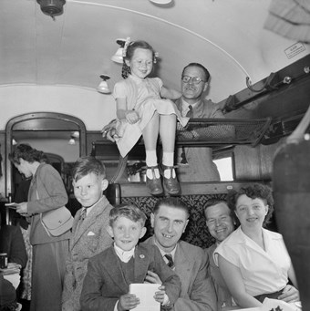 A group of people in a train carriage. Two men sit with a boy and a woman on their knees. Above, a young girl sits on a luggage rack and a man stands on the seat beyond. They all wear suits and dresses, and are smiling. The image is in black and white.