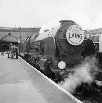 The engine of a steam train alongside a platform. On the front of the engine is a sign with the word 'LAING' beneath two crossed flags, and 'STAFF OUTING CORONATION YEAR' around the edge. Steam rises from beneath the engine.