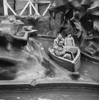 A boat travels along the channel of a water ride. In the boat, a smiling woman sits beside a young boy. A man sits in the prow and wipes his hands with a handkerchief. To the left is a false rocky outcrop of the ride. The image is in black and white.