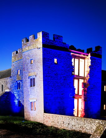 an old building or a castle with brickwork illuminated in blue. Central section shows windows lit up at night.