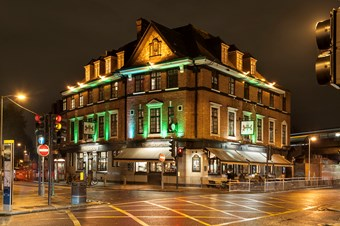 Large detached four-storey building lit up at night with white and green light. There are people sitting around tables outside on the right hand side of the building. There's a road with traffic lights, street lights and traffic signs on the foreground. In the background there is dark sky.