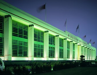The famous Art Deco Hoover Building lit up in green light at night time. There is a vegetation border in the foreground while the background shows a dark blue sky.