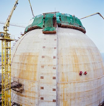 The image depicts a large dome which is white with specks of orange colouring. At the top, there is green netting and scaffolding. To the left there is a large yellow crane. On the dome itself, there are two people who are abseiling.