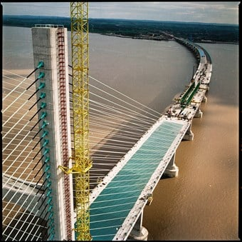 A view of the top of a bridge, which spans out to the coastline in the distance. The bridge is not yet finished. The river underneath it is a muddy-brown colour.