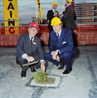 Two men wear suits and crouch down to plant a small tree. They are both wearing hard-hats. In the background, there are three other men. To the left of the picture, there is a large vertical sign saying 'Laing'.