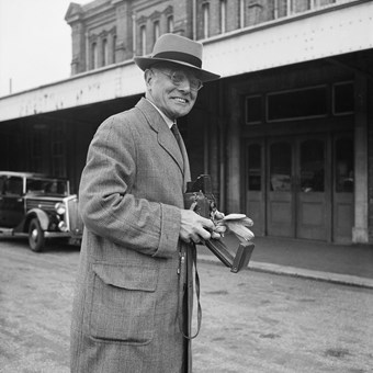 An old man smiles to the camera. He is holding a camera and wears and overcoat and hat. In the background there is a building and an old car. The image is in black and white.
