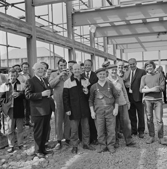 A crowd of men pose for a picture. Some are wearing work-overalls and donkey jackets and a few of the men wear suits. Some of the men are holding pints of beer. They look to be celebrating inside a large building which has scaffolding on the outside of it.
