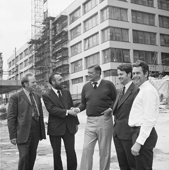 Five men pose for a photograph; all wearing smart clothes. The man in the middle shakes the hand of the man to his left. They are all smiling. In the background, there is a building site.