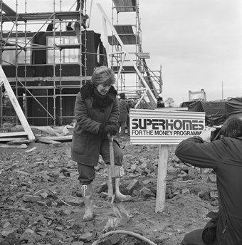 A woman plunges a shovel into the earth.  Next to her is a sign saying 'Superhomes For the Money Programme.' Behind her there is scaffolding around a half-built house. The image is in black and white.