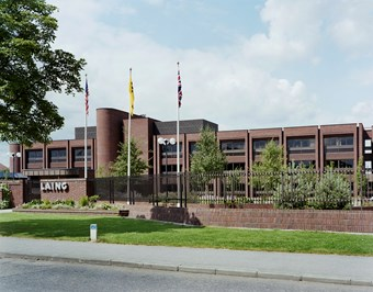 An exterior view of a large brick-coloured building. Three flags stand out the front. A Laing sign is posted on the front of the building. In the foreground, there is a hedge and a tree.