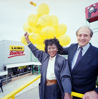 A man and woman pose for a picture. The man is on the right and wears a blue business suit. The woman on the left wears a grey suit and holds yellow balloons. In the background, there is a grey building with the title 'Laing Toolhire' on it.