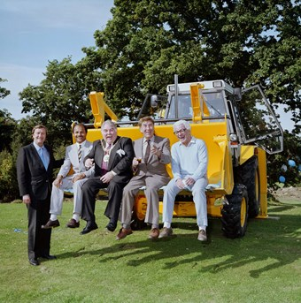 Five men in suits pose for a photograph. One man stands to the left of the picture. The other four sit in the digger of a JCB. In the background there's a tree.