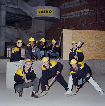 Eight men wear black and yellow donkey jackets and pose for a photograph. Each man holds a shovel as if they were doing a dance move. They pose in a dark room and it looks like it is underground. In the background, the Laing logo can be seen.