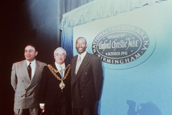 Three men pose for a picture and all of them wear suits. In the middle, the man wears an ornamental necklace showing he is a mayor. In the background there is circular sign on a blue background a sign saying 'Linford Christie MBE. Birmingham'. In the bottom left of the image, there is the shadow of a photographer.