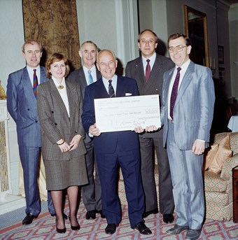 Five people pose for a photograph. There are four men and one woman. The man in the middle holds a large cheque. The photograph is in colour and all the people are smartly dressed.