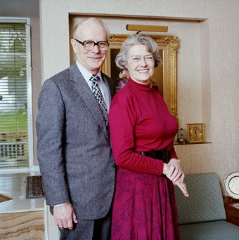 A smartly dressed couple pose for a photograph. The man stands on the left wearing a grey suit. The woman on the right wears a red blouse. They look to be standing in an office.