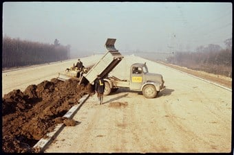 A long road recedes into the distance. A truck dumps a load of earth in the middle of the road, where a worker drives a small digger. The truck has a 'Laing' sign on it. Another worker stands next to the truck. He has an L on his back.