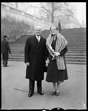 A smartly dressed man and woman pose for this black and white photo. The man wears a suit and the woman wears what looks to be a fur scarf. In the background there's a wide set of stone steps and a leafless tree.
