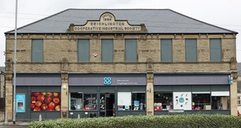 Shop front with windows blocked up on first floor and the words 'Erected 1886 Drighlington Co-operative Industrial Society' carved in stone plinth above the gutter