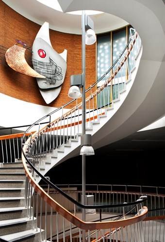 Spiral staircase with a sculpture on the wall