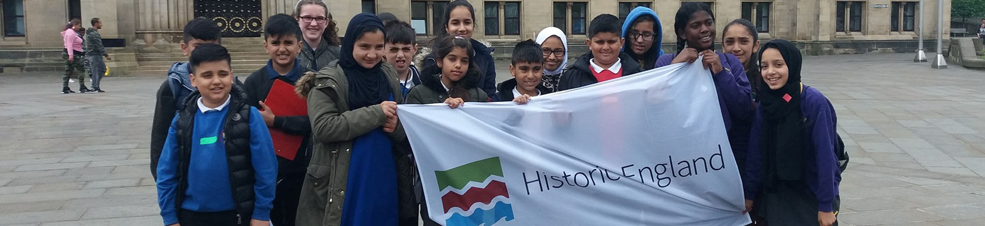 Pupils outside Bradford City Hall holding a banner with the Historic England logo on it.