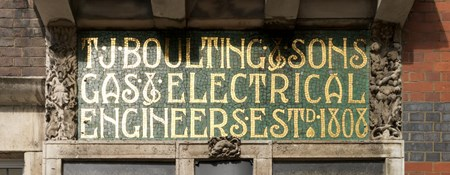 Signage in gold letters with green background. The signage is surrounded by brickwork and other architectural features