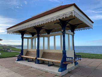 Shelter with ornate rooftop, blue pillars, and a wooden bench. Sea is visible in the background