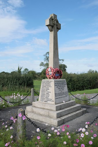 War memorial with a cross on top with a wreath of poppies
