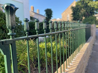 Green railings in focus set in a brick wall with a garden in the background that is not in focus