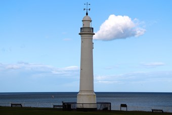White lighthouse with blue sky in the background. Single cloud next to the lighthouse