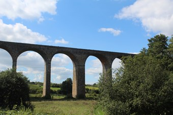 Rural setting. Large viaduct with arches framing the scene. Blue sky above the viaduct track